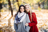 Full length portrait of a young woman posing with girlfriend in autumn park - 182819870
