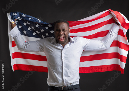 African American man holding a flag of the United States of America stands on a dark background.