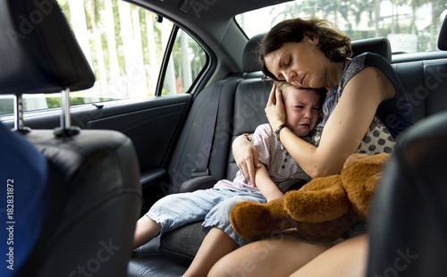 Mother consoling her crying son in the car