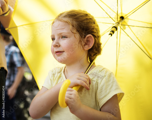 Closeup of young caucasian girl with yellow umbrella