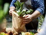 A seller putting vegetable in a bag - 182836094