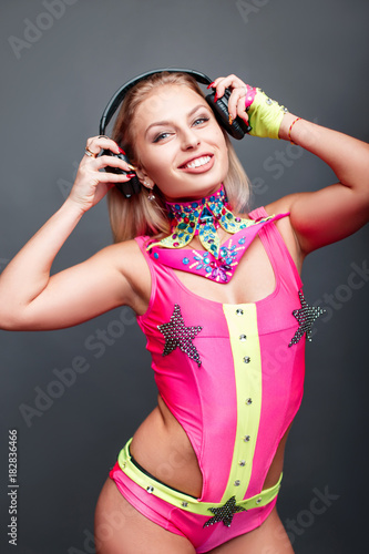 Happy young woman dancer with headphones in pink go-go costume listening music on gray background Poster