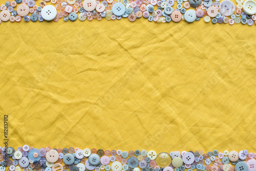 top view of colorful buttons frame on yellow cloth background with copy space
