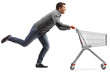 Guy running and pushing an empty shopping cart isolated on white background