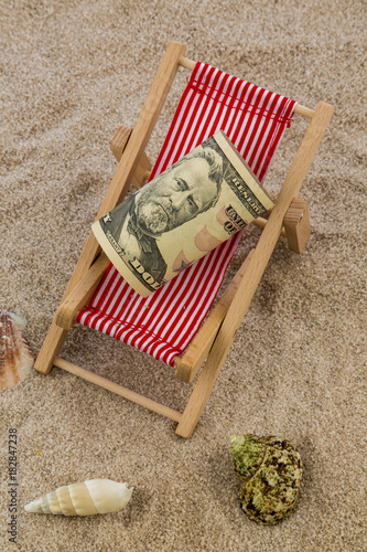 deck chair with piggy bank and dollars