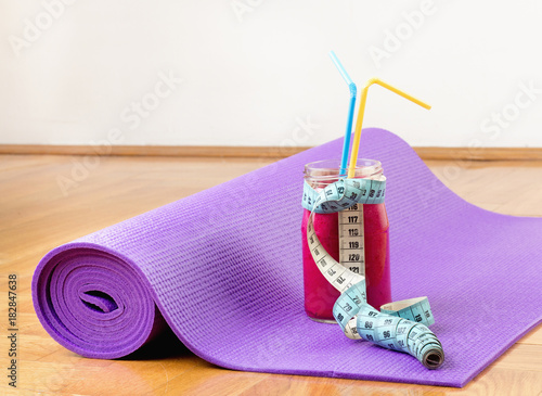 Fototapeta Smoothie and measuring tape on yoga mat