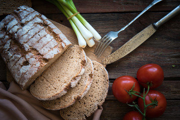 Fresh brown bread on a wooden plate with vegetables