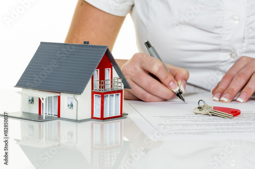 woman signs purchase contract for home - 182850837