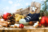 St. Nicholas Day, Children's shoe with sweets, gifts and christmas ornaments on rustic wood, light blue snowy background, in Germany called Nikolaus - 182854656