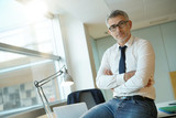 Confident businessman sitting on desk with arms crossed - 182861865