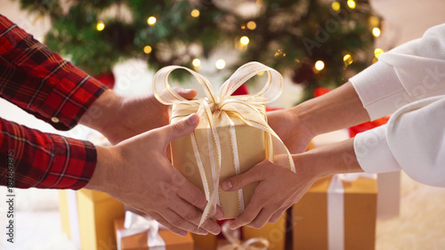Fototapeta close up of couple hands with christmas gift box