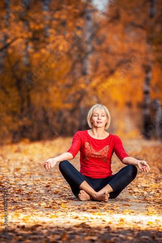 Naklejka beautiful woman doing yoga outdoors On yellow leaves