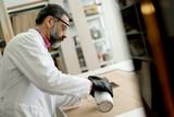 Engineer in the laboratory examines ceramic tiles - 182875296