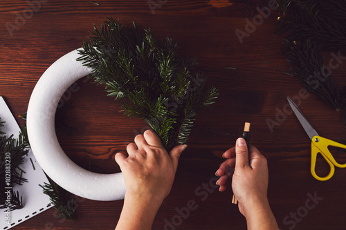 Female florist fixing branches on christmas wreath, top view - 182883230