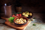Tapas bowl with shrimps or prawns in garlic olive oil, potatoes, tomatoes and herbs on a rustic wooden table, spanish appetizer, dark background with cop space - 182885454