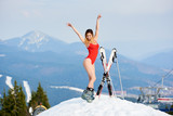 Happy beautiful female skier wearing red bodice, posing with skis and poles on the top of the mountain. Winter ski resort, forests, ski slopes and ski lift on the background - 182891469