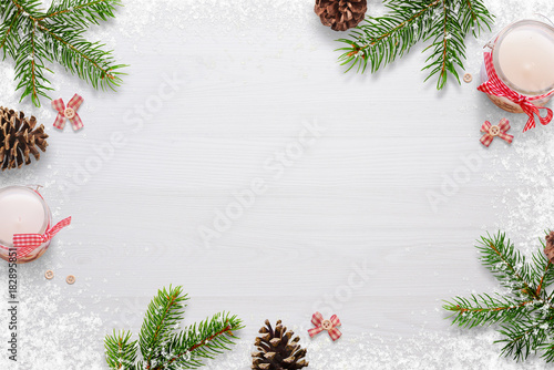 Foto Murales Flat Christmas background scene with fir branches, bows, candles, pinecones and snowflakes Free space for copy text on white board. Top view.