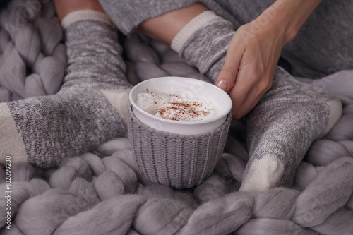 Female feet wearing cozy warm wooleen socks. Warmth concept.Woman covered with warm blanket drinking coffee in bed close up .