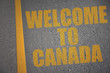 asphalt road with text welcome to canada near yellow line.