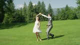 SLOW MOTION Newlyweds happily dancing in park after their wedding. Young man and woman waltzing on grass on a sunny day. Husband spins his beautiful wife and they bow to each other at the end of dance - 182902470