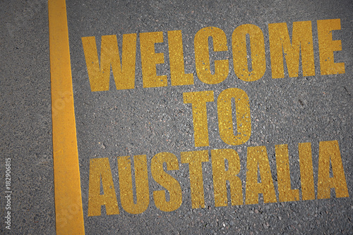 asphalt road with text welcome to australia near yellow line.