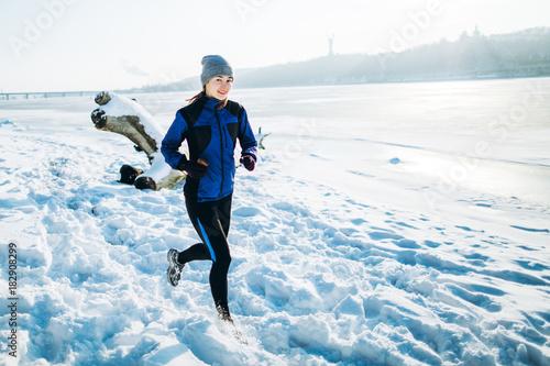 Fit slim woman running through the deep snow
