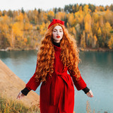 Red-haired woman with long curly hair in a red coat and a green turban on a bright autumn background. Girl on the background of a lake with blue water - 182911477