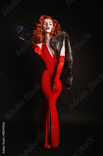 Fototapeta Red-haired woman with curly hair in red dress and long gloves smoke on black background. Girl is dressed in retro style with natural fur and the mouthpiece with a cigarette