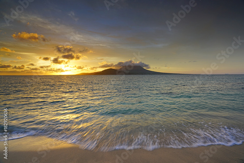 Foto op Canvas Zee zonsondergang Sunset view of the Nevis Peak volcano across the Caribbean Sea from St Kitts