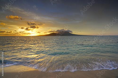 Staande foto Zee zonsondergang Sunset view of the Nevis Peak volcano across the Caribbean Sea from St Kitts