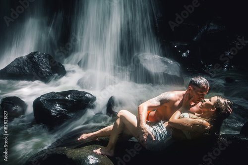 Erotic couple kissing near waterfall. Traveling at Bali. Plakát