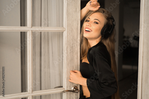 Fotobehang Muziek Closeup portrait of a young woman listening to music in headphones