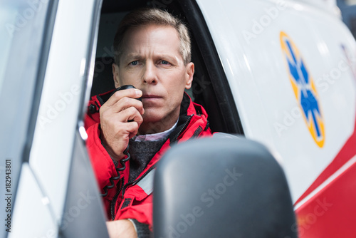 Sticker handsome middle aged paramedic talking by portable radio