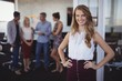 Portrait of smiling young businesswoman standing at creative