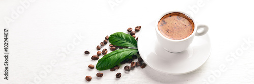 A cup of coffee and coffee beans on a wooden background. Top view. Free space for text.