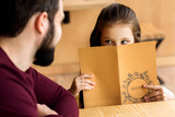 cropped image of daughter looking out from restaurant menu - 182947217