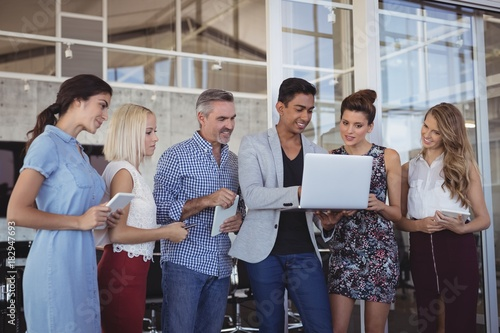 Young businessman explaining team over laptop