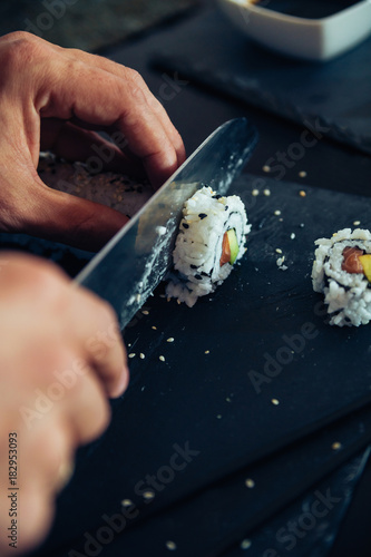 Tuinposter Sushi bar Sushi Being Cut