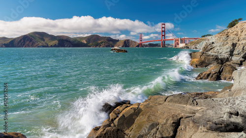 Panoramic view of famous Golden Gate Bridge seen from scenic Baker Beach in sunny day with blue sky and clouds in summer, San Francisco, California, USA