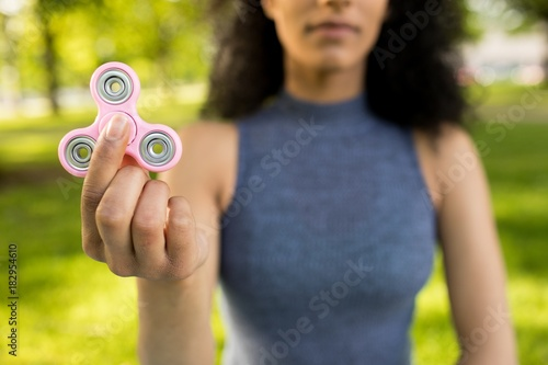 Foto op Canvas Amusementspark Girl holding a fidget spinner in a park