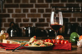 traditional italian pasta with tomatoes and arugula in plate and glass of red wine - 182966083