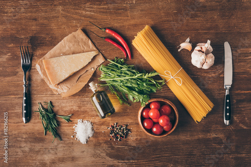 Poster top view of row pasta, fresh ingredients, Parmesan, fork and knife on wooden tab