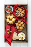 spanish tapas finger food, baked olives, shrimps, potatoes, tomato and garlic dip, party appetizers on a dark wooden tray with a red napkin on white painted wood, flat top view from above - 182966832