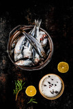 Fresh raw fish with rosemary, lemon and salt on dark rusty background, copy space top view - 182966852