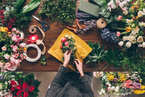 cropped image of female florist wrapping bouquet in pack paper