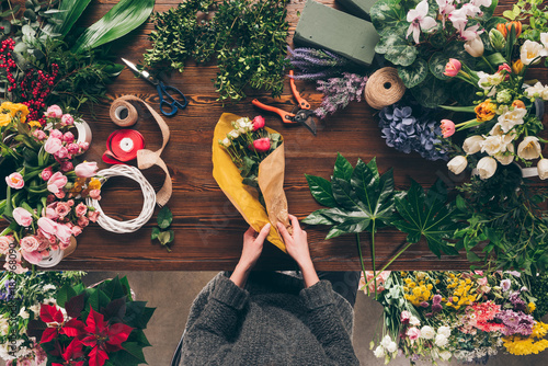 cropped image of florist wrapping bouquet in yellow pack paper