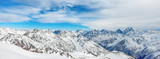 Mountains in snow. Panorama of winter landscape with peaks and blue sky