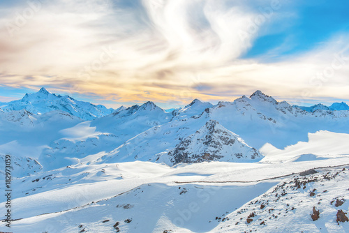 Mountains with snow peaks and sunset sky
