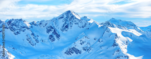 Staande foto Panoramafoto s Mountains in snow. Panorama of winter landscape with peaks and blue sky