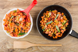 Bowl and frying pan with vegetable mix, spatula on table - 182979048
